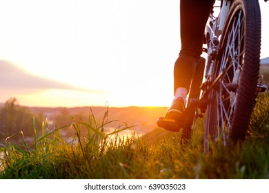 girl riding bike in sunset light, wheels and legs close up