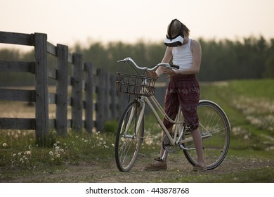 Girl Riding a Bike with a VR Headset