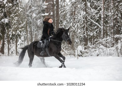 A girl riding black horse through snow in winter forest on background, side view
