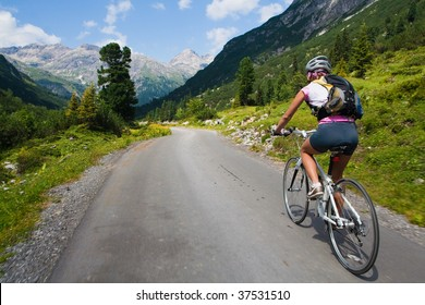 Girl riding fast on a bicycle in mountain area. Back view and motion blur