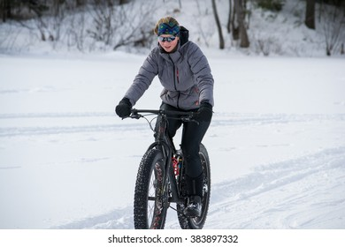 Girl riding a fat bike on a lake in winter