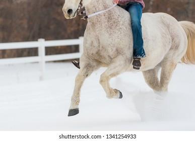 girl riding horse bareback along white fence. Winter scene with snow