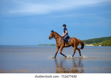 Girl riding a horse on coastline at the beach in early morning
