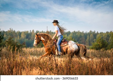 Girl riding on the Appaloosa horse on the field in the tall yellow grass trees and sky background