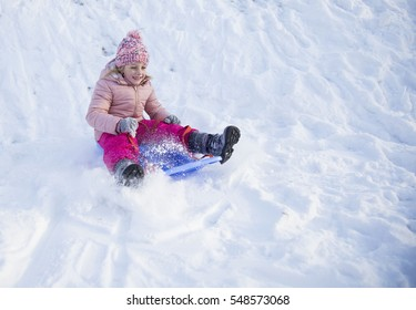 girl riding on snow slides in winter time
