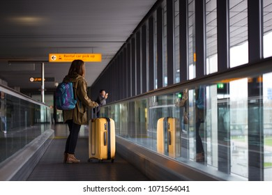 the girl is riding on the travolator at the airport with a large yellow suitcase
