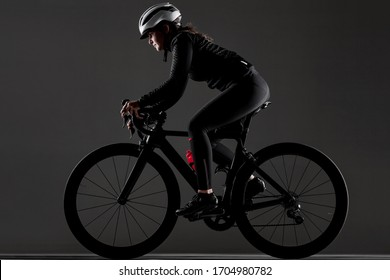 Girl riding road bike. Studio shot against dark background.