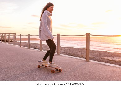 Girl riding a skateboard near the beach at sunset.
