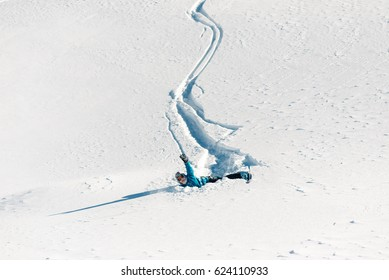 girl is riding with snowboard from powder snow hill and fall down
