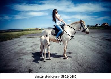 A girl riding a white horse