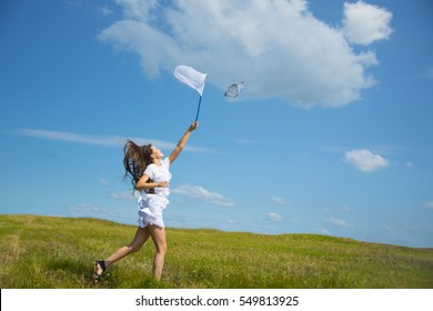 girl with a ring-net on a summer filed. Sunny day. smiling girl holds butterfly net on blue sky with clouds Cute young adult caucasian woman catching a butterfly in scoop-net. Female with long hair