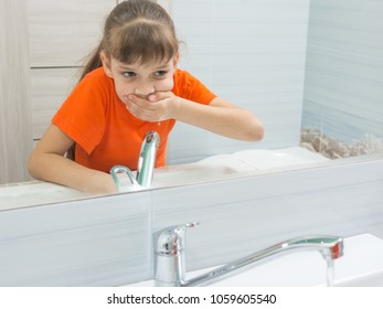 The girl rinses her mouth after brushing her teeth