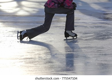 the girl rises after a fall skating on the ice rink