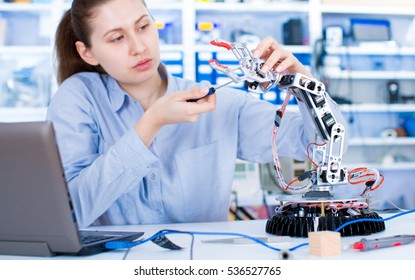 Girl in robotics laboratory. Young woman technician repair roboter manipulator