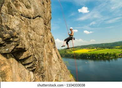 Girl rock climber abseiling above Vltava river on beautiful sunny day, Czech republic