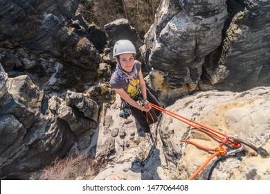 Girl rock climber abseiling from sandstone towers, Tisa sandstone rocks, Usti nad Labem region, Czech republic