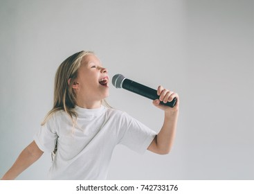 Girl Rocking Out. Image of a child singing to the microphone, isolated on light. Emotional portrait of an attractive kid on a gray background.