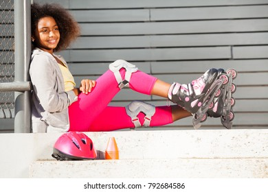 Girl in roller blades sitting on steps of park