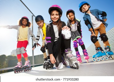 Girl in rollerblades playing with friends outdoors