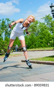 Girl roller-skating in the park, she is still studying, and nearly falls