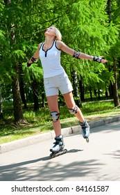 Girl roller-skating in the park at summer