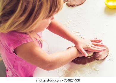 girl is rolling out dough to make cookies, preparation for the holiday