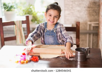 The girl rolls the dough for cookies in the kitchen