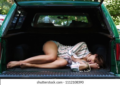 The girl with the rope-bound hands, unconscious, lies in the trunk of the car. Ability to crop the image to the size of the rear door of the pickup truck in order to create a 3D sticker. Daylight