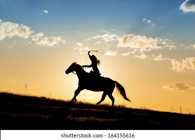 Girl roping while riding hose with beautiful sunset behind her