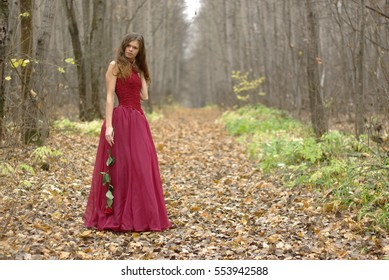Girl with a rose in the autumn forest