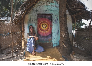 A girl in round glasses, a blue skirt and a psychedelic shirt in the form of a hippie, sits at a bungalow with a decorated art door, on which the heart is depicted