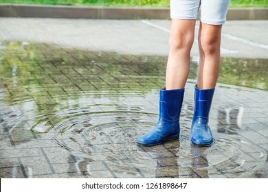 girl in rubber boots standing in a puddle after a rain outdoor on summer day. legs closeup