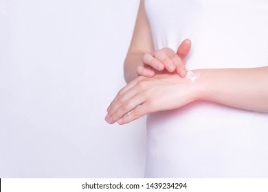 The girl rubs the healing ointment into the wrist joint against pain and inflammation in the joint, White background, copy space, stiffness
