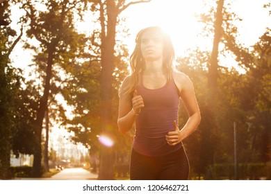 Girl run in the autumn park. Morning run with headphones. Sport with music. Sunlight.