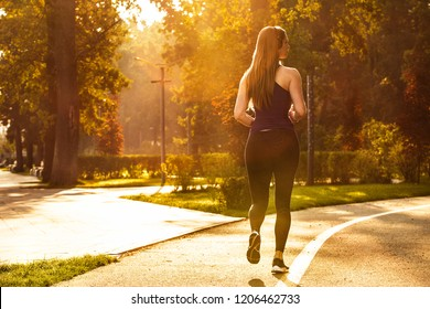 Girl run in the autumn park. Morning run with headphones. Sport with music. Sunlight.