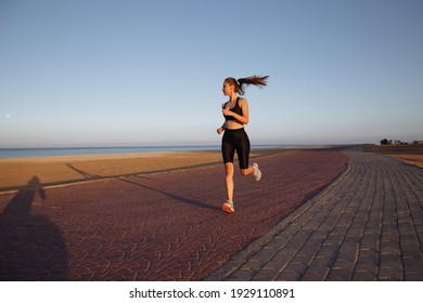 girl runner in a black tracksuit and sneakers runs by the sea during sunset