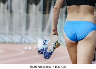 girl runner holds in hands spike running shoes after sprint race