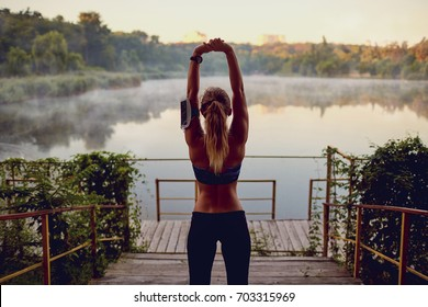 Girl runner on a warm-up before jogging in the morning by the la