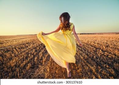 girl running across field in the sunset