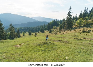 girl running across meadow with mountain view
