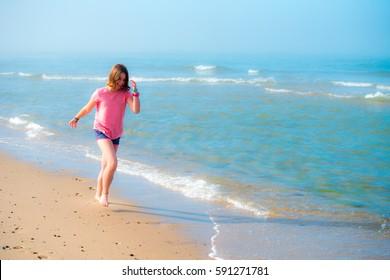 Girl running along a beach