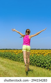 Girl running along the field with sunflowers on a sunny summer day