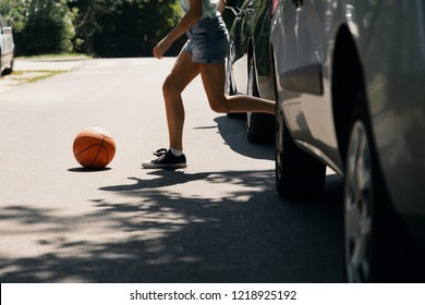 Girl running with ball on pedestrian crossing next to cars