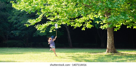 A girl running barefoot with a bug net