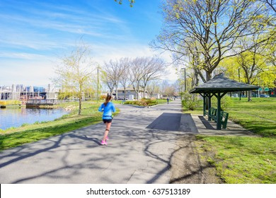 A girl is running in The Esplanade of Boston, located in Boston, Massachusetts, USA.