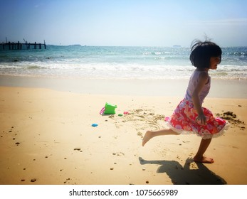 A girl is running happily on the beach.