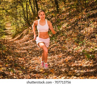 Girl running up Hill in park woods on trail