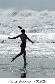 Girl running into ocean