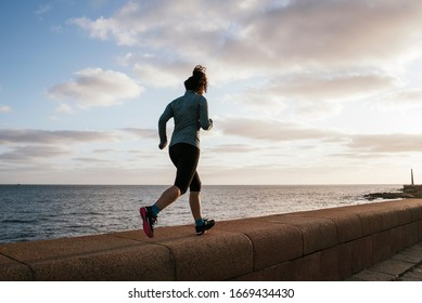 girl running near the sea, exercising on a pier with sportswear, backwards