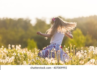 Girl running on the field of dandelions on summer sunset. Beautiful little kid girl  dancing on dandelion meadow with sunset. Summer fun outdoors.